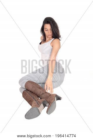 A lovely young Hispanic woman sitting in gray leggings an brown boots on the floor looking down isolated for white background.