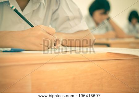 Blurred of Asian girls students writing test exams on paper for Admissions in high school with uniform student in row seat School classroom of Thailand taking exam background and education concept
