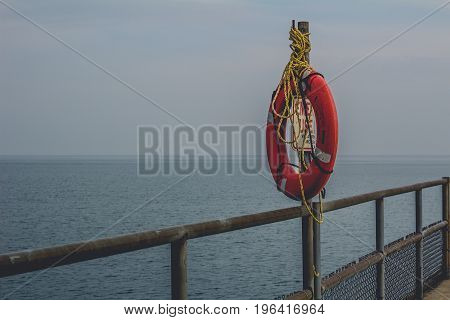 A life preserver on the metal railing of a pier.