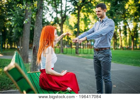 Romantic date of couple on a bench in summer park