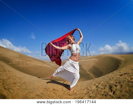 young happy woman standing on sand dunes in summer windy day