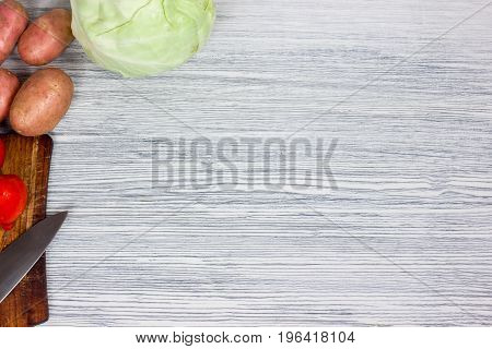 Assorted fresh vegetables with knife on rustic white wooden background: tomatoes, cucumbers, bell pepper, green and purple onion. Top view point.