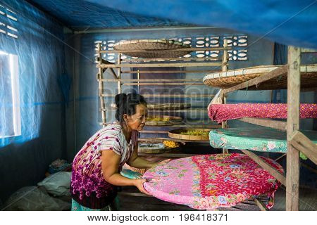 villagers of Ban Sanuan Nok Buriram Province. Thailand - April 30 2017: old women activists are presenting silkworms in farm.traditional thai fabric at Burirum Thailand. The local silk cloth is characterised by elaborate patterns and design