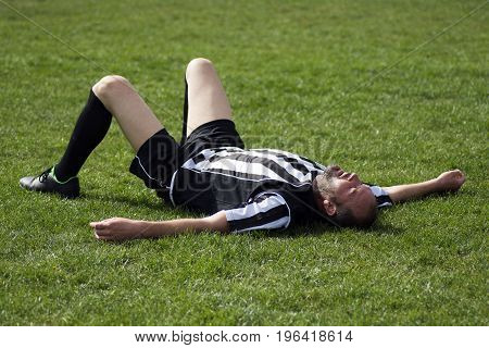 The tired soccer player is lying down on the grass on playing field finished football match.