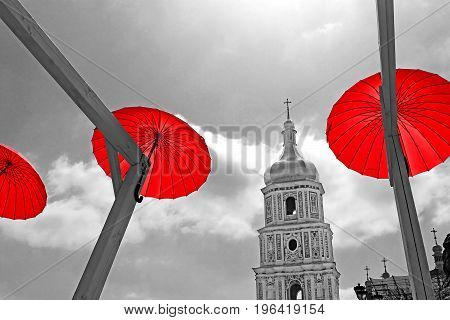 KYIV, UKRAINE - MAY 01, 2017: Bright red umbrellas decoration in fan zone for international song competition Eurovision-2017 on Sofia square in Kyiv. Partially applied black and white filter