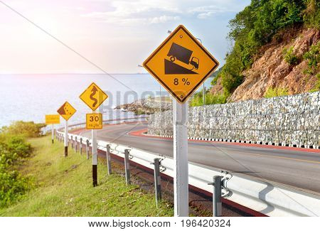 warning symbol sign for traffic protecion in the mountain road photo in sun lighting.