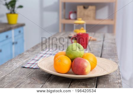 Close up view on fruit on a table at kitchens wooden table. Bright apples and oranges on front view with teaspot and red mug on background.