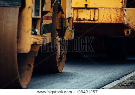 A yellow asphalt compactor aligns the road. Laying new asphalt.