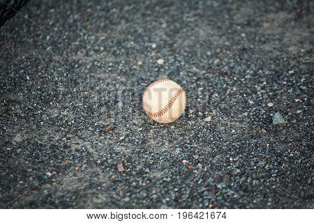 Worn Baseball Laying on the ground in Rocks