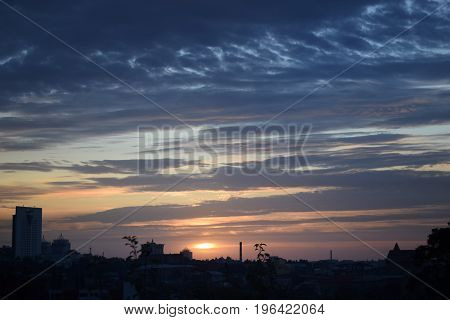Landscape of the City area. The picturesque colourful sky in decline dawn sunrise. The sun on the horizon the horizon. Warm colors.
