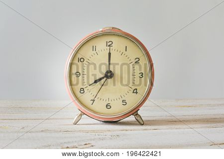 Retro alarm-clock with time of on white wooden table and pink pastel background.