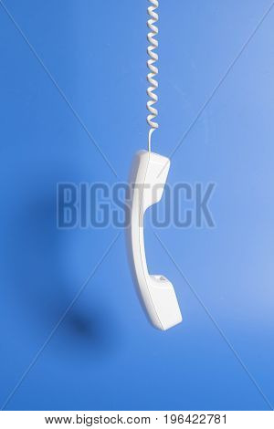 Telephone Receiver And Cord On Blue Background.