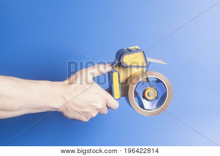 Man holding an industrial tape dispenser on blue