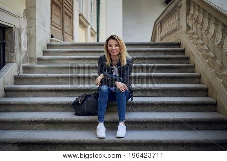 Outdoor portrait of young smiling blond-haired woman sitting on steps