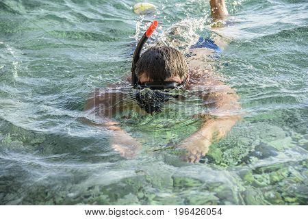 Man in a diving mask with a pipe in sea water.