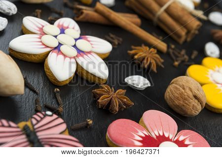 Gingerbread cookies with nuts and spices, colorful homemade cakes in shape of flower on black textured background, selective focus