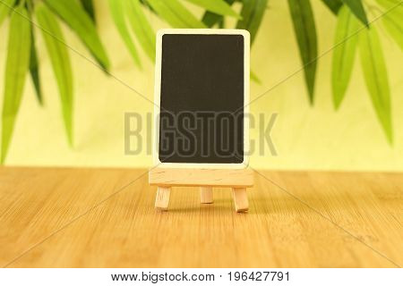 Small empty slate in height to write a message that is posed on an easel all on wooden floor and green foliage background