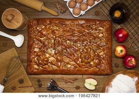 Apple pie with baking ingredients, spices and kitchen tools for cooking, rustic homemade sweet food on wooden table, top view