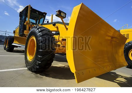 Road grader, huge powerful construction machine with big yellow scoop and black wheels, heavy industry, bottom view, blue sky and white clouds on background