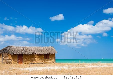 Colorful adobe house next to the sea under blue sky