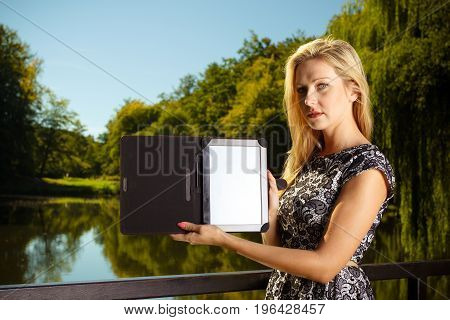 Technology outdoor relaxation concept. Woman in park relaxing and using tablet ebook spending her leisure time outside