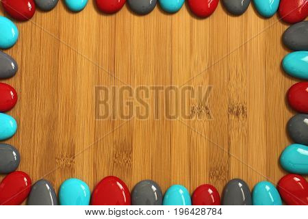 Small red gray and blue pebbles arranged all around a brown bamboo wood floor with an empty space to write a message