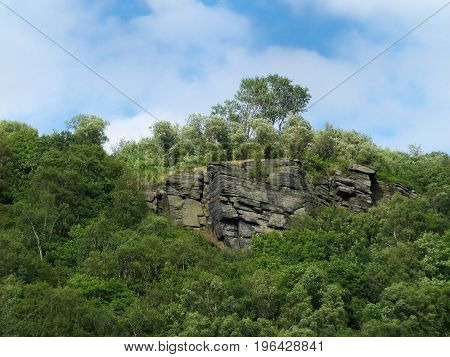 gritstone outcrop surrounded by forest in the pennine landscape near hebden bridge west yorkshire.