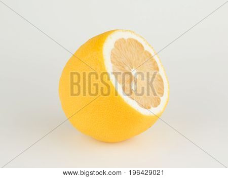 large ripe lemon with a cut off tip on a white background