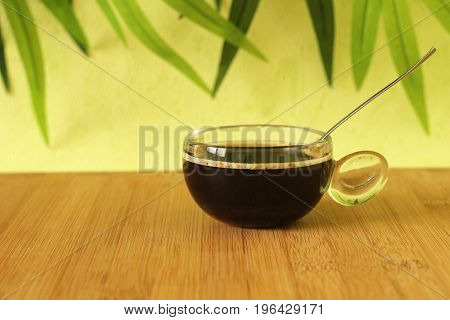 A cup of black coffee on a brown bamboo wood floor with a spoon on a green foliage background