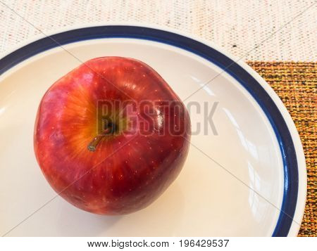 Healthy and tasty food. Delicious red ripe apple in white ceramic bowl on towel