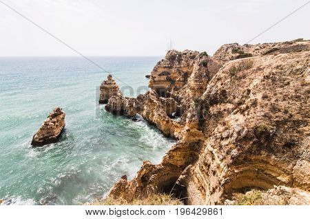 Travel To Stunning Rocks Cliffs With Seas Caves On Sandy Camilo Beach In Colorful Sunny Blue Sky