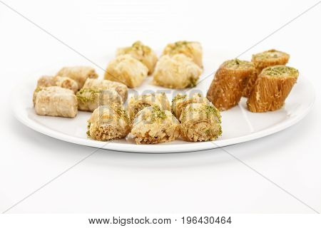 Crispy assorted baklava bites arranged on a plain plate. Five pieces of Kol W Shkor cashew baklava decorated with chopped pistachio crumbs in the front. Closeup studio shot on white background.