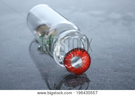 Bottle with contact lenses on gray table