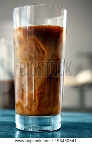 Glass with cold brew coffee and milk on wooden table