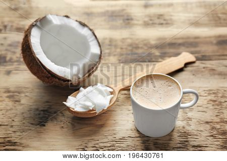 Cup of tasty coconut coffee and spoon with butter on wooden table