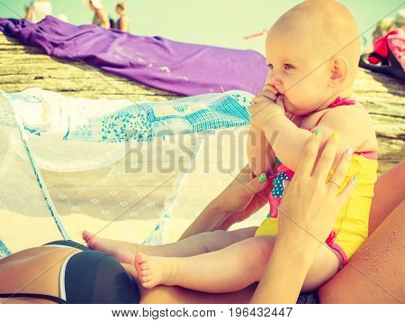 Baby lying on mother belly in swimsuit on beach