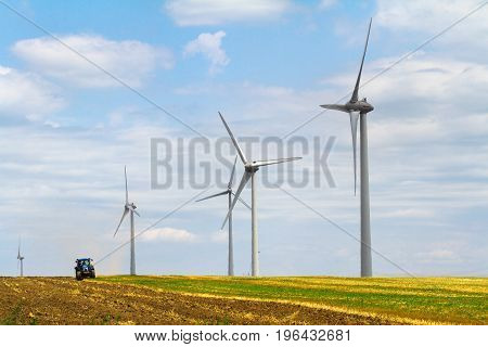 row of eolian wind turbine on a meadow with tractor ploughing the land in the background on a sunny day blue sky with clouds