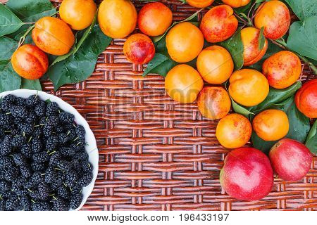 On the wicker table lie orange apricots and a plate with mulberry.
