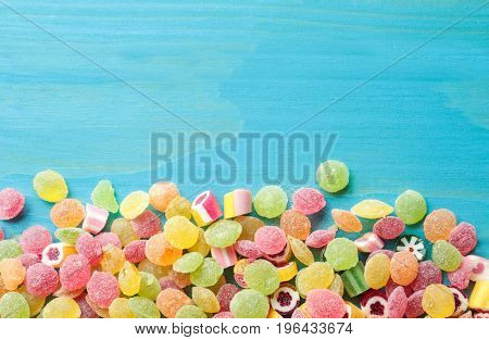 Tasty colorful candies on wooden background