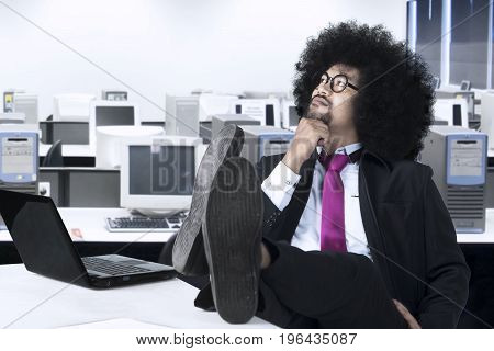 Image of African businessman daydreaming with laptop and his foot on the table while sitting in the office