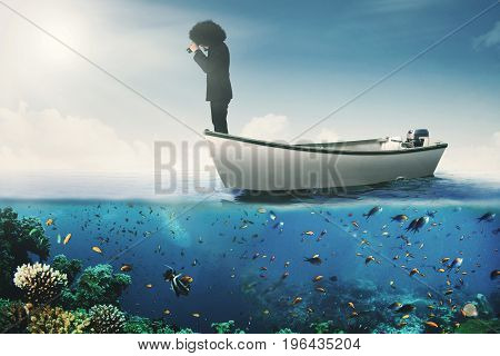 Portrait of african businessman standing on the boat while looking through binoculars at the sea