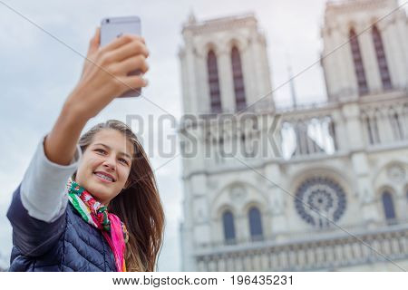Teenager tourist girl is taking selfie on cathedral of Notre Dame de Paris with mobile smart phone. Travel, tourism, vacation concept. France.