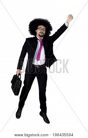 Full length of Afro businessman with curly hair leaping in the studio while holding a briefcase and wearing formal suit