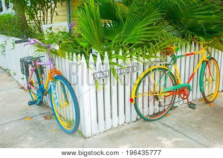 Key West, USA - June 26, 2012; Two brightly painted bicycles leaning on picket fence on residential street corner