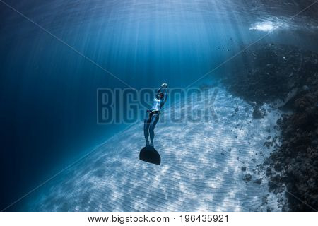 Woman freediver glides over sandy bottom of a crystal clear tropical sea