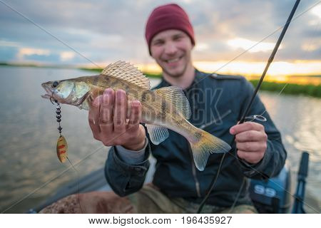 Happy fisherman with fish on the lake