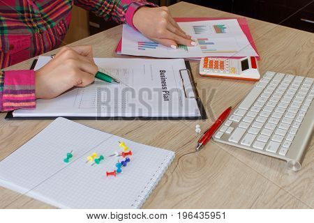 Person woman pointing writing goals on a paperwriting business plan at workplace Female holding pens papers notes in documents Saving money concept. Business plan calculator dollar banknote on the table