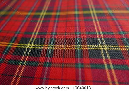close up of Tartan textile pattern consisting of criss-crossed horizontal and vertical bands in multiple colours.