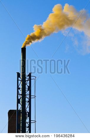 Dark Smoke From A Chimney Against Blue Sky