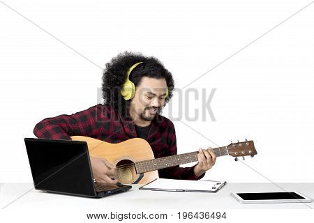 Image of young Afro man playing a guitar while composing a song isolated on white background